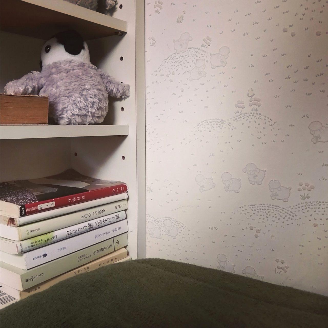 お気に入りの本と雑貨が並んだ寝室の棚の写真。