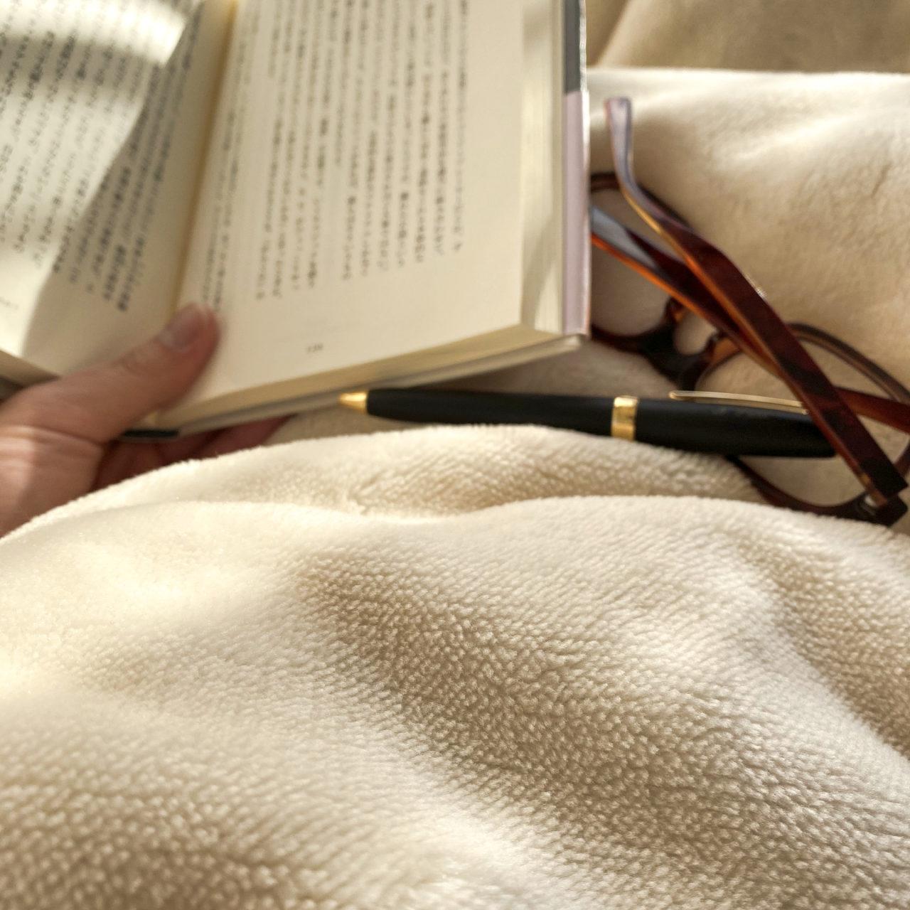 毛布にくるまり本を読んでいる