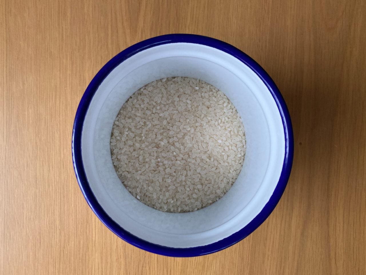 ホーローの米びつに米を収納しているようす