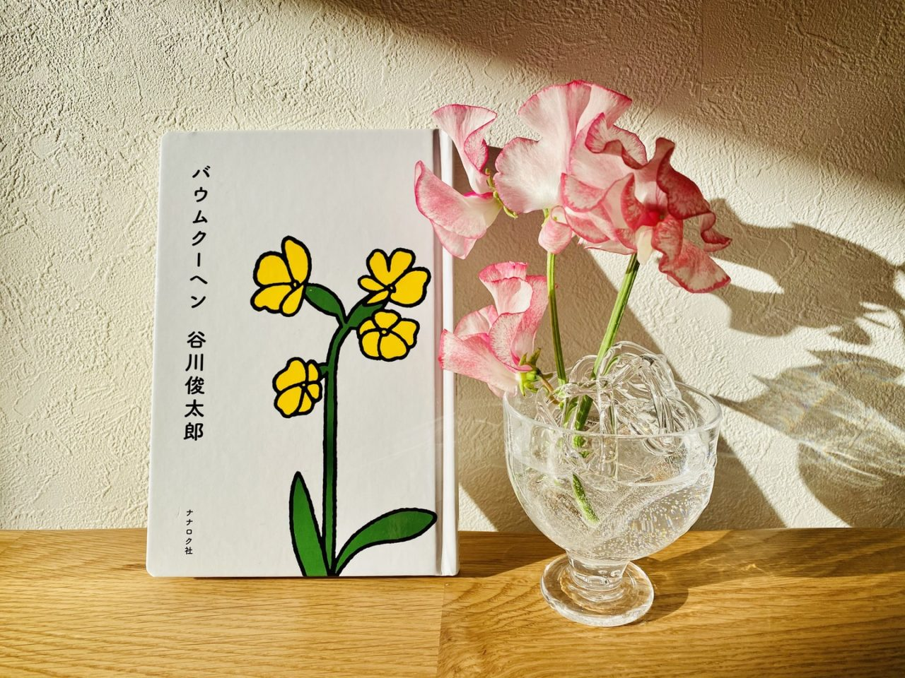 詩集とピンク色の花の画像