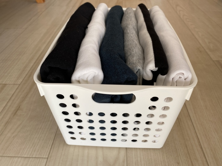 バスケットにtシャツを立てて収納している。