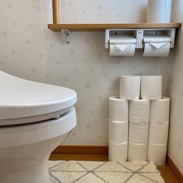 トイレ内の床に積んであるトイレットペーパーの画像