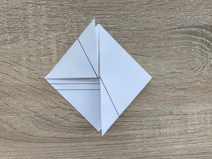④折った両端の下の部分を更に半分に折り曲げて、反対側の頂点部分に合わせます。