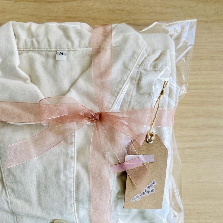 洋服を透明な袋へ入れて、ニュアンスピンクのオーガンジーリボンを結んだラッピング