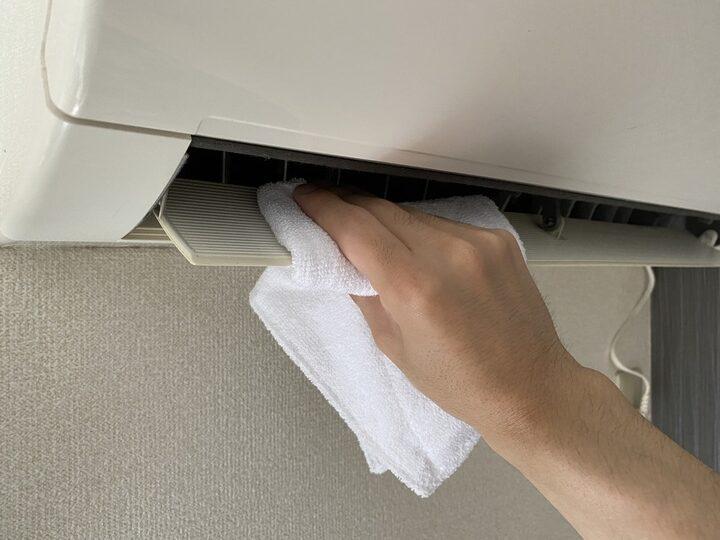 エアコンの吹き出し口を掃除している