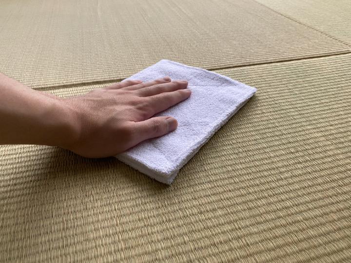 畳を拭いて掃除している